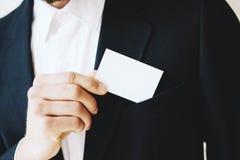 商人去掉从他的夹克口袋的一张空白的白色名片 水平的大模型,被弄脏的背景 免版税库存图片