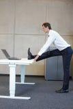 商人锻炼在办公室 免版税库存照片