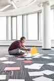 商人组织的照片,当坐地板在创造性的办公室时 库存图片