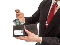 商人从他的钱包里面拉智能手机现金 图库摄影