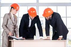 商人建筑师在工作 三businessmеn建筑师遇见 免版税库存照片