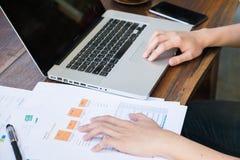 商人从纸板料的分析数据在木桌上 免版税图库摄影