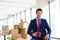 年轻商人画象喝与移动的箱子的咖啡在背景在办公室 图库摄影