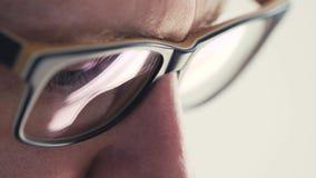 年轻商人画象的关闭戴眼镜的研究计算机 股票录像