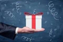 商人` s手出现和一个小礼物盒与站立在黑板背景的一把红色弓 图库摄影