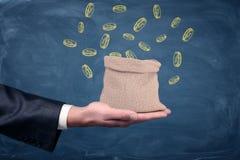 商人` s手出现和站立对此的一个小金钱袋子与在蓝色背景的拉长的硬币 库存照片