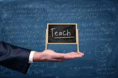 商人` s手拿着有词的一个小画架黑板教对此与在背景的等式 免版税库存图片
