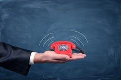 商人` s棕榈举行有显示soundwave放射的线的一个小红色减速火箭的拨号电话 库存图片