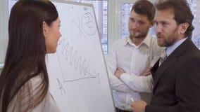 商人explaines某事在对他的伙伴的活动挂图 影视素材