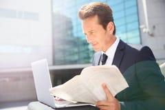 商人hoding的报纸和研究膝上型计算机 免版税库存照片