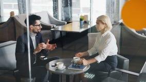 商务伙伴分享新闻的男人和妇女谈话在咖啡的咖啡馆 股票录像