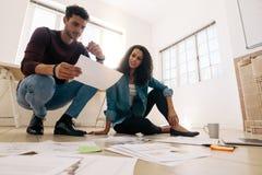 商务伙伴坐地板和与事务一起使用 免版税库存照片