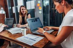 商务伙伴开坐在有膝上型计算机的书桌的会议在会议室 库存照片