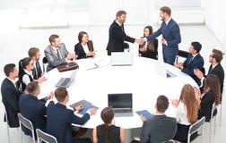 商务伙伴握手在谈话靠近圆桌 库存照片