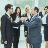 商务伙伴握手欢呼的企业队背景的  免版税库存图片