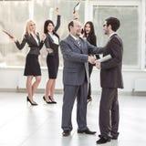 商务伙伴握手欢呼的企业队背景的  库存图片
