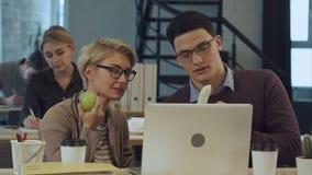 年轻商务伙伴在办公室休息,吃果子和谈话 影视素材