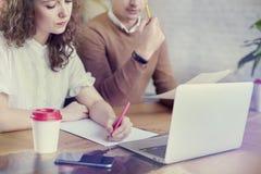 年轻商务伙伴的人民,谈论创造性的想法在办公室 使用现代膝上型计算机,食用咖啡 免版税图库摄影