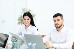商务伙伴的图象谈论文件和想法在会议上 免版税库存照片