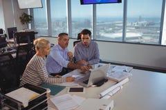 商务伙伴谈论在膝上型计算机在会议 库存照片