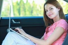 商务旅游:有膝上型计算机的繁忙的女实业家在汽车 免版税库存图片