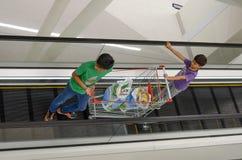 商城的孩子与购物车 免版税图库摄影