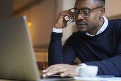 商学院的非裔美国人的学生黑暗的毛线衣和白色衬衣的在有连接的现代膝上型计算机到无线互联网 免版税库存图片