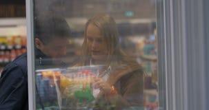 从商店冷冻机的年轻夫妇采摘食物 股票视频