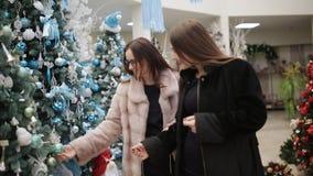 商店圣诞节的两名妇女为假日选择圣诞装饰 股票视频