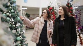商店圣诞装饰的两名妇女考虑人为圣诞树和圣诞装饰 股票视频