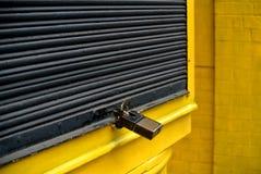 商店快门结束了黄色和黑与挂锁 图库摄影