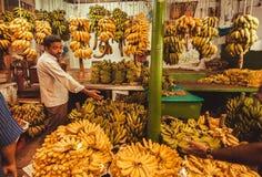 商店用香蕉和人买的果子在农夫市场上 图库摄影