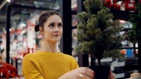 商店的年轻可爱的深色的女孩选择一棵人为圣诞树,圣诞节装饰 库存照片
