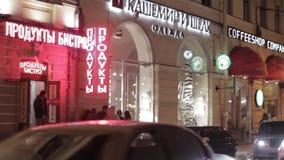 商店红色和白色牌看法夜街道的 驾驶汽车 人们 股票视频