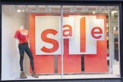 商店购物中心在窗口的销售标志与母时装模特 免版税库存照片