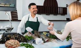 商店雇员快乐的销售的鲜鱼和变冷的海鲜 免版税库存照片