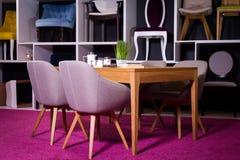 商店,家具销售在购物中心 用餐与纺织品椅子的博览会样品木桌在一个白色架子w的灰色 免版税库存图片