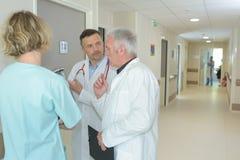 商谈在医院走廊的医护人员 图库摄影