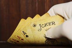 啤牌卡片在白色手套的一只手上 库存图片