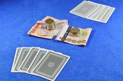 啤牌卡片在蓝色天鹅绒桌等待的挑战的折叠和金钱赌注 库存照片