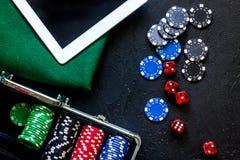 啤牌在一台金属案件、绿色赌博的布料和片剂计算机设置了在一个灰色台式视图 免版税库存照片