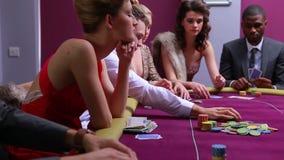 啤牌的人们制表参加红色的礼服的位于打赌妇女所有 股票录像