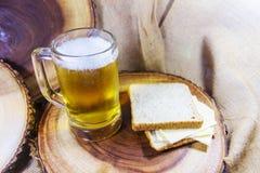 啤酒、乳酪和面包在木板材作为背景 库存照片