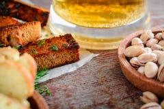 啤酒、开心果和黑麦油煎方型小面包片 免版税库存图片
