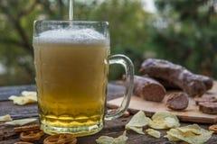 啤酒、香肠和椒盐脆饼在室外的木板 10月 免版税库存图片