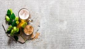 啤酒、绿色蛇麻草和麦芽石表面上 免版税库存照片
