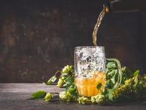 啤酒从瓶倒入在黑暗的土气木背景用蛇麻草,正面图的杯子 库存图片