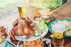 啤酒党和烤鸡愉快享用在家 库存图片