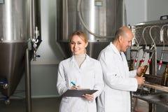 啤酒厂工厂的两名工作者 库存图片