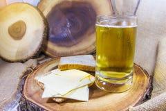 啤酒和乳酪用面包在木板材背景 库存照片